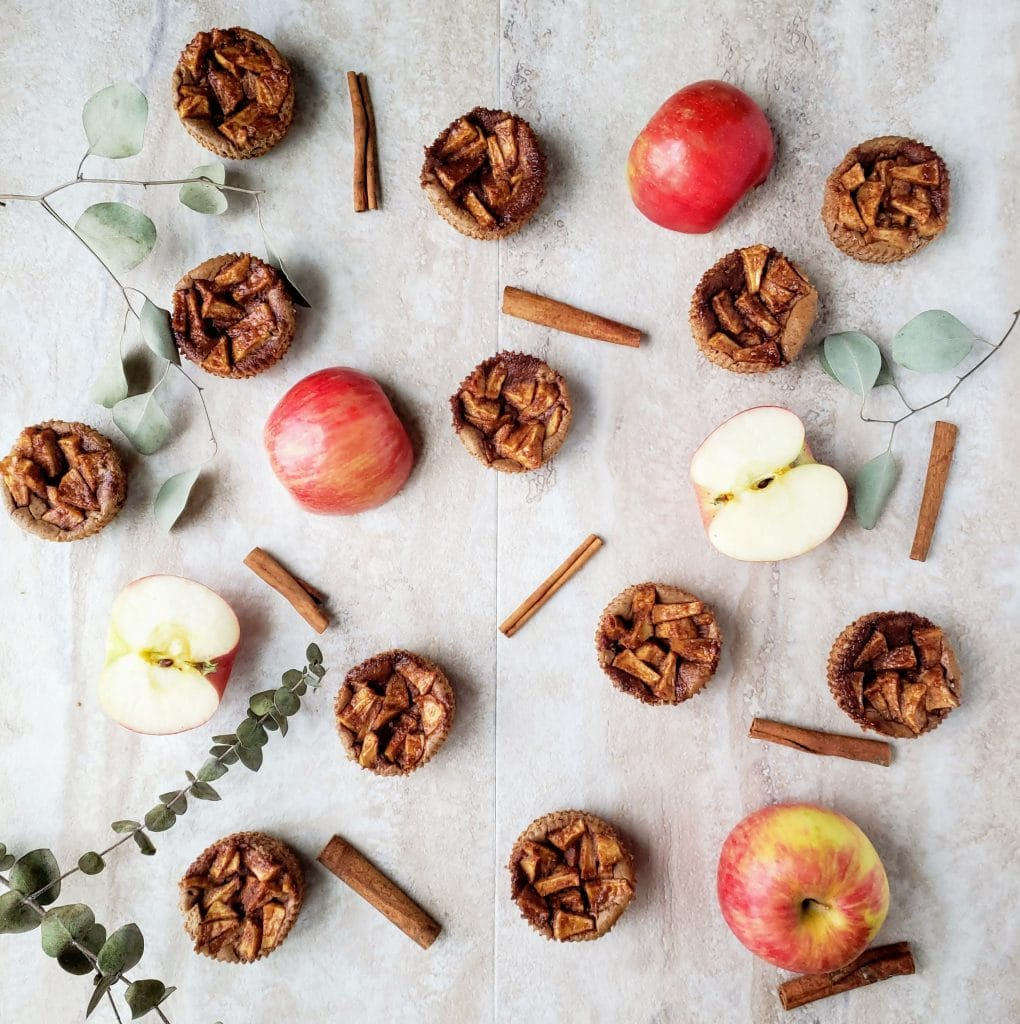 overhead shot of mini apple pie cheesecake surrounded by cinnamon sticks and fresh apples.
