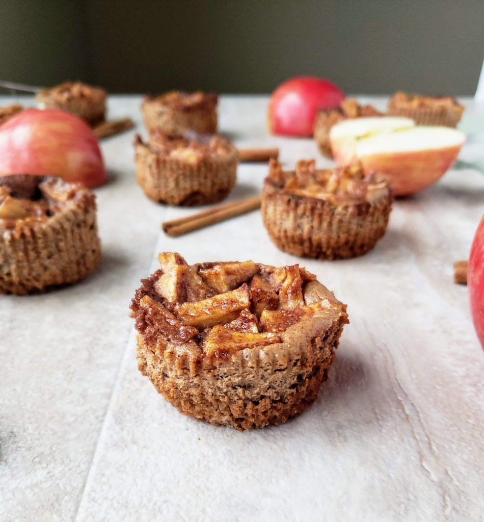 close up of a mini apple pie cheesecake surrounded by apples and cinnamon sticks