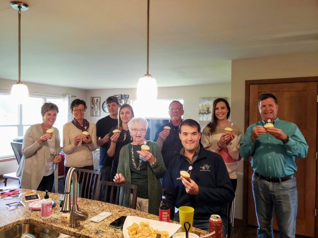 family holding cupcakes before a gender reveal