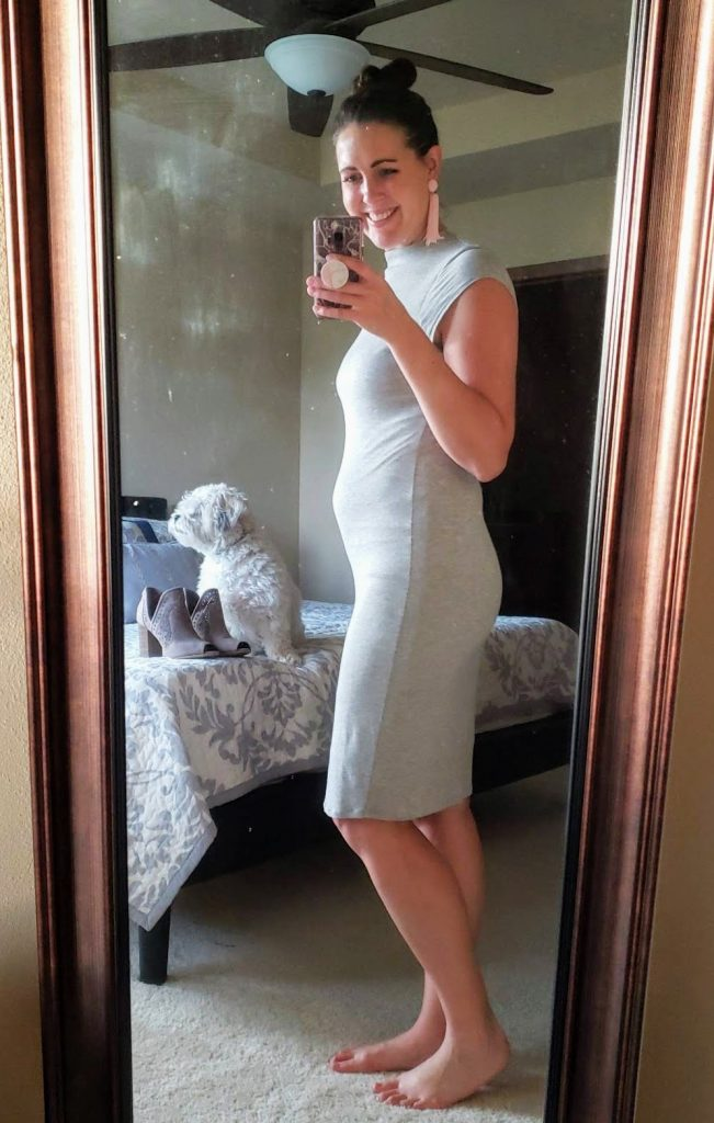 woman in a gray dress showing off her pregnancy belly
