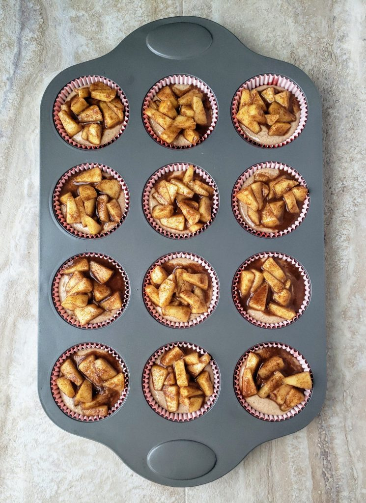 cheesecakes topped with diced apples ready to be baked