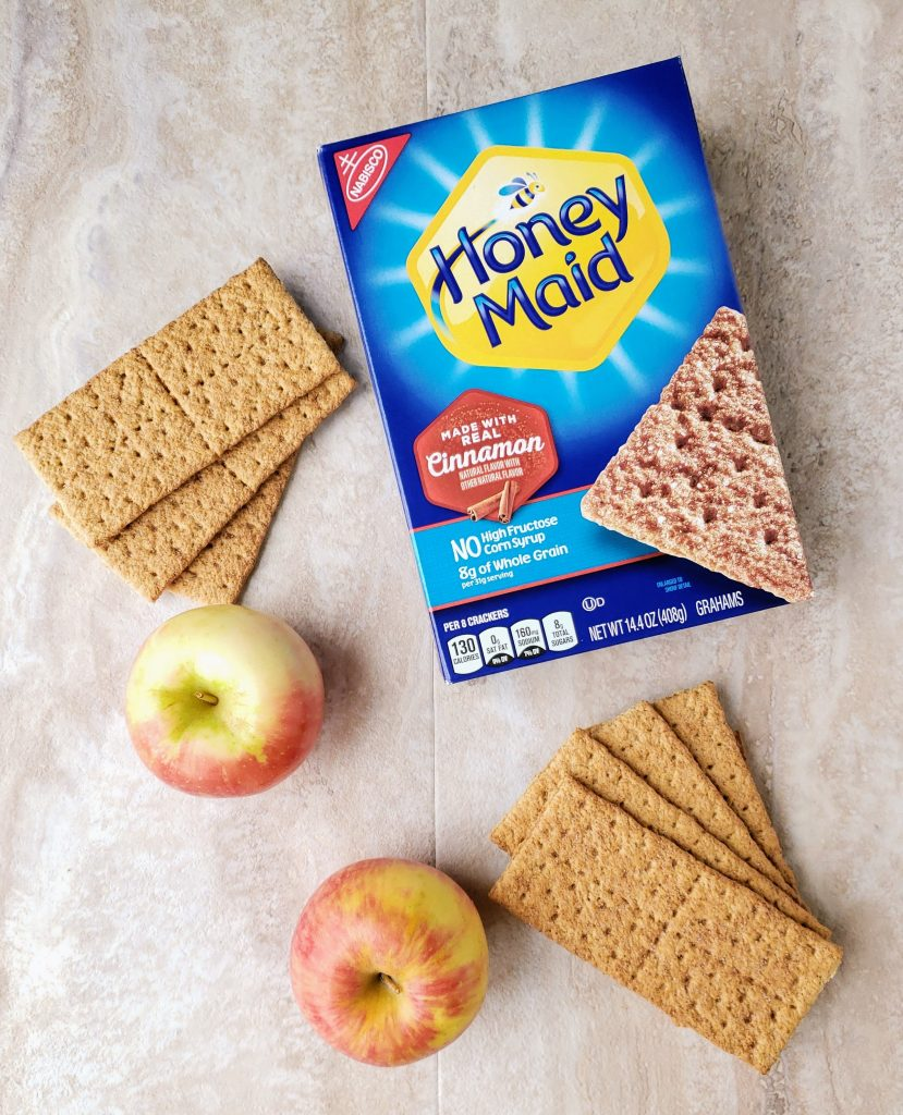 box of graham crackers with graham crackers next to it and fresh apples