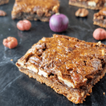 slices of healthy pecan pie bars on a black table