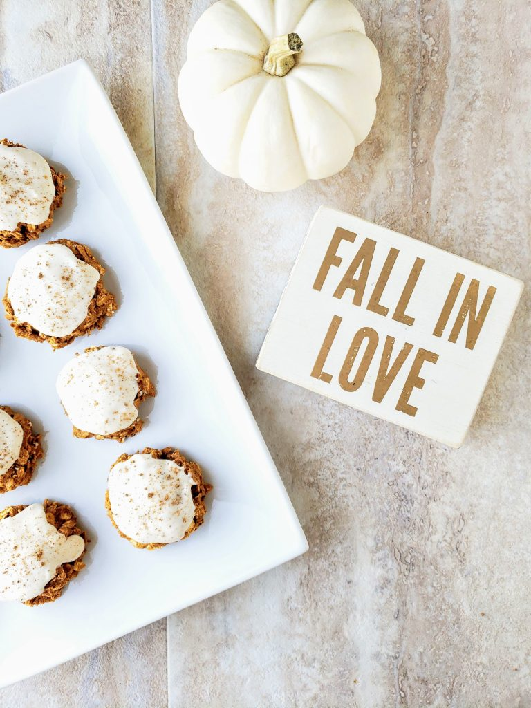 "frosted pumpkin oatmeal cookies on a white plate next to a white pumpkin and a ""fall in love"" sign"