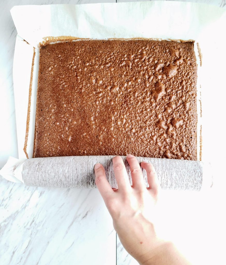 Hand rolling a baked chocolate cake