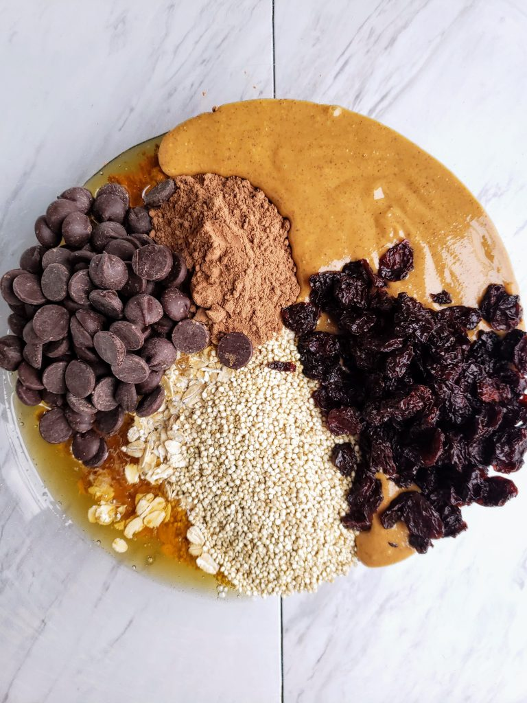 bowl filled with energy bite ingredients: dry quinoa, dried cherries, dark chocolate chips, oats, peanut butter, honey, cocoa powder