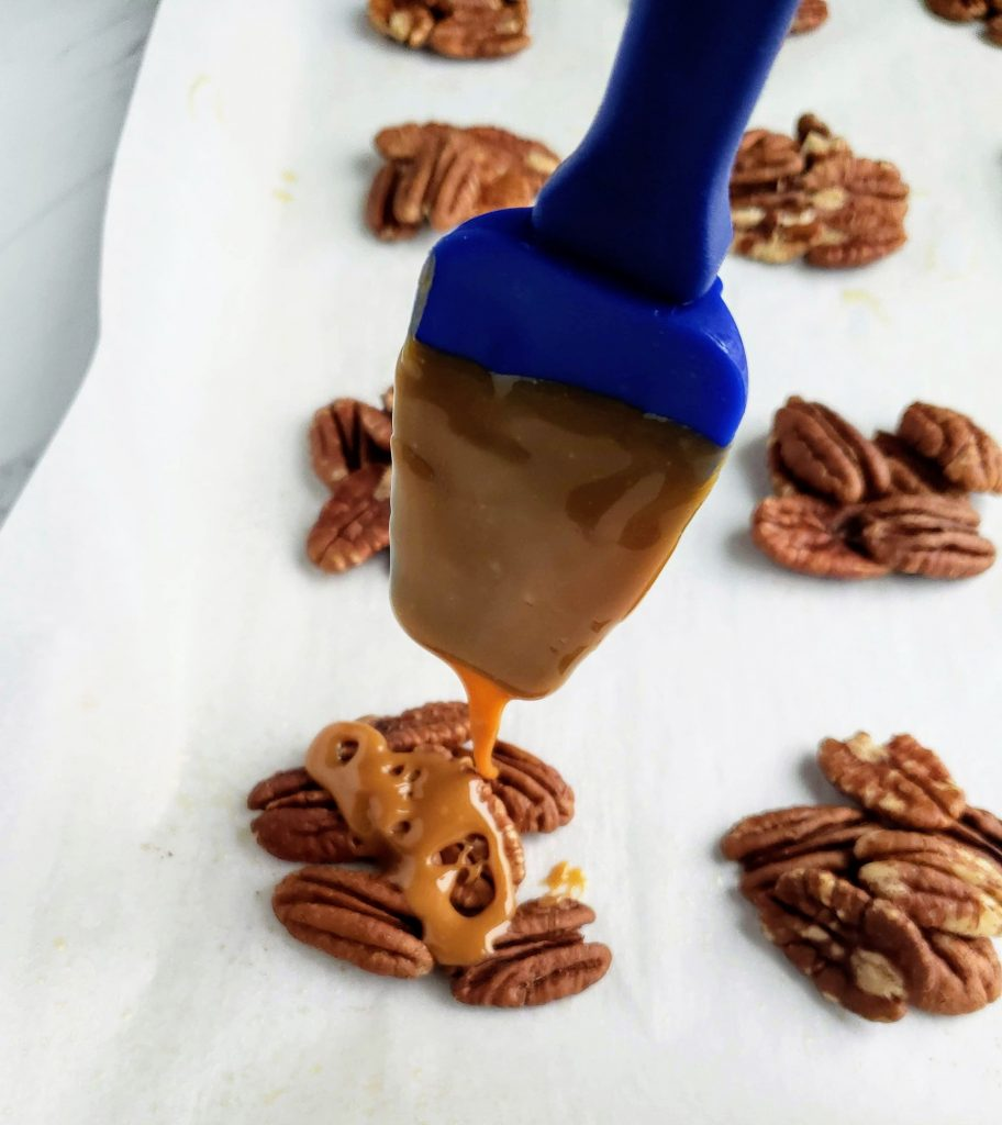 drizzling caramel sauce over pecan clusters