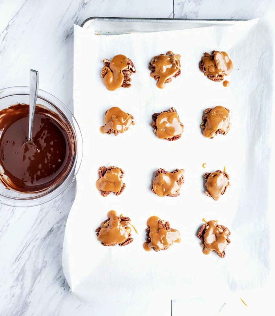 pecans covered in caramel sauce on a baking sheet sitting next to a bowl of melted chocolate