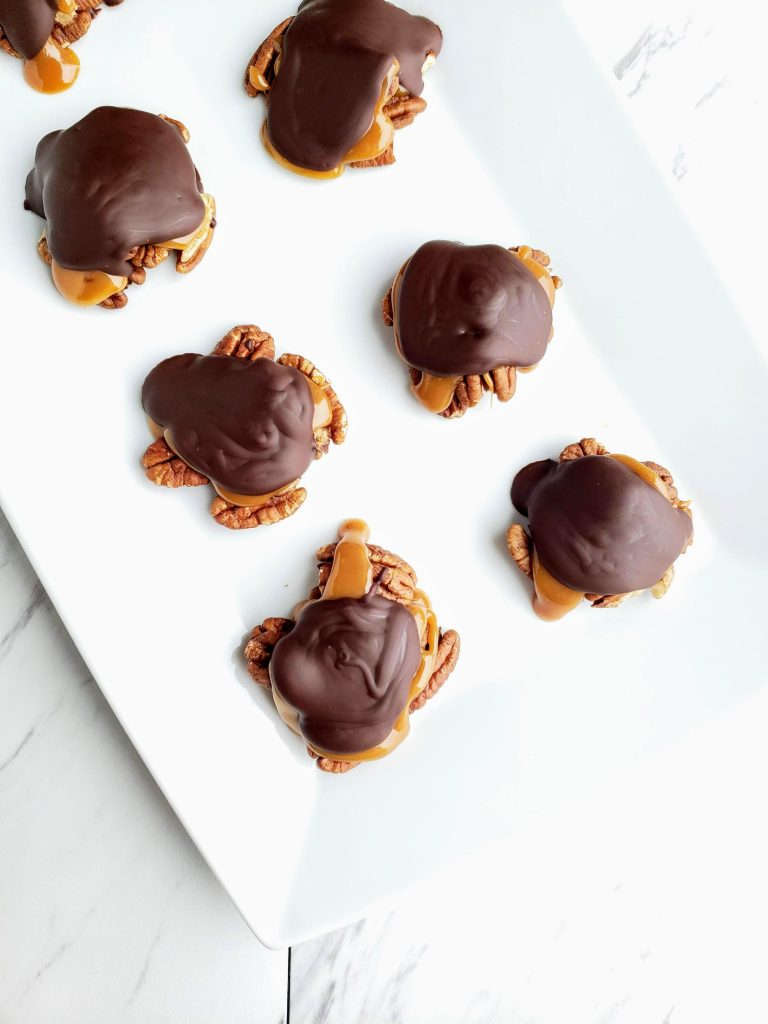 chocolate pecan turtle clusters in even rows on a white plate
