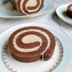 slice of chocolate eggnog cake roll on a light blue plate with the remaining cake roll in the background