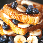 Stack of french toast slices with bananas and blueberries