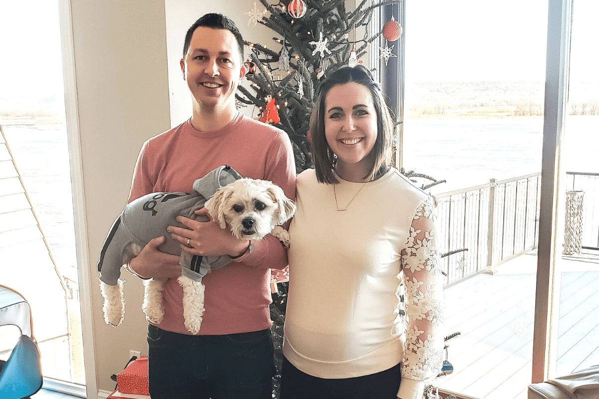 a couple with a dog standing in front of a Christmas tree