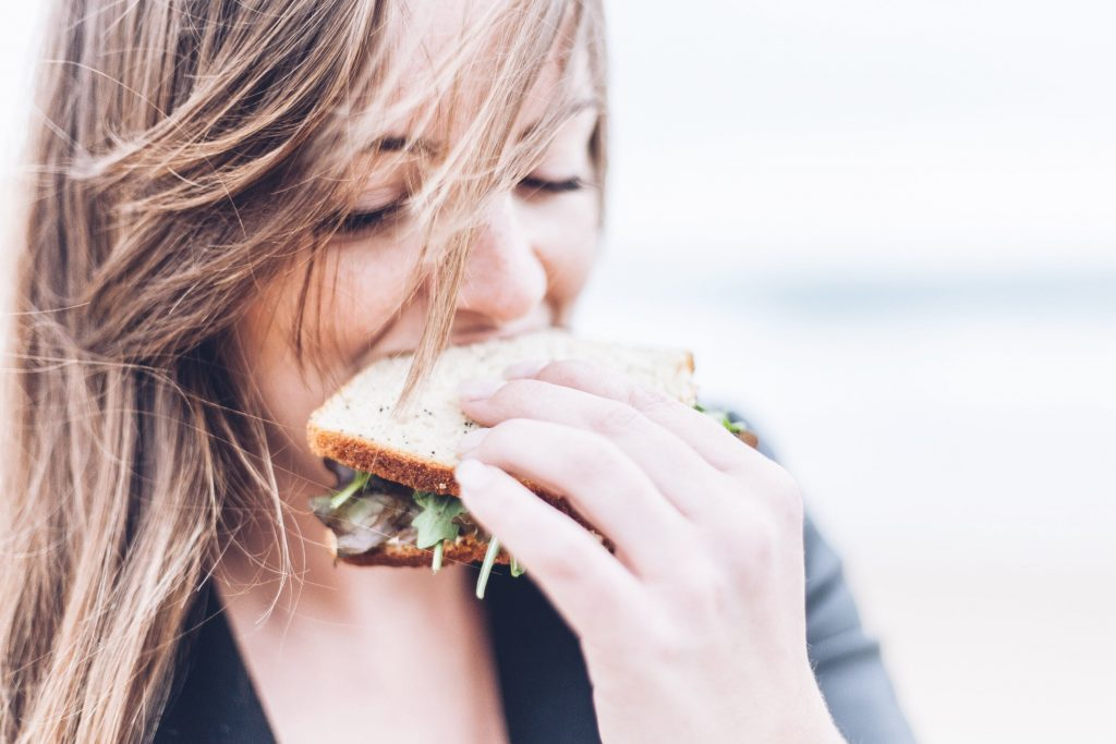 woman with long brown hair eating a sandwich