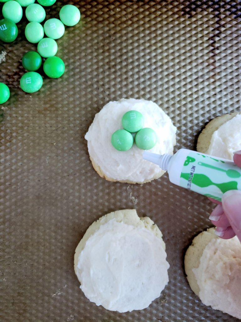 four cream cheese cookies with M&Ms in a shamrock shape