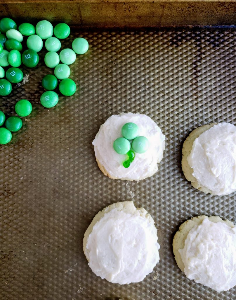 four cream cheese cookies on a cookie sheet with one shamrock cookie created