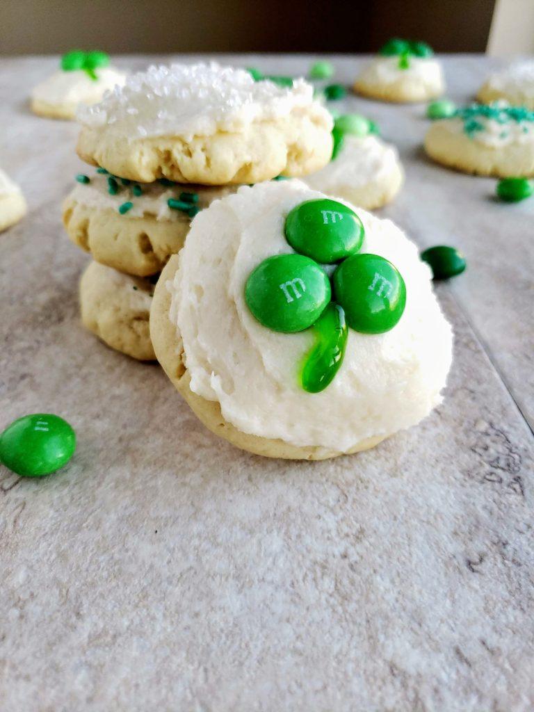 stacked cream cheese cookies, with a shamrock cookie leaning against the cookies