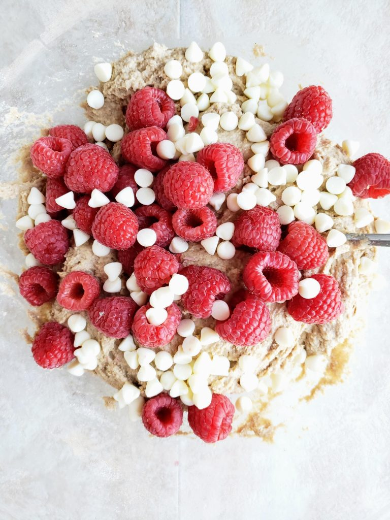 Bowl of raspberry scone batter with fresh raspberries and white chocolate chips on top