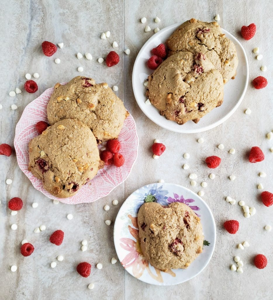 raspberry white chocolate scones on three different plates surrounded by fresh raspberries and white chocolate chps