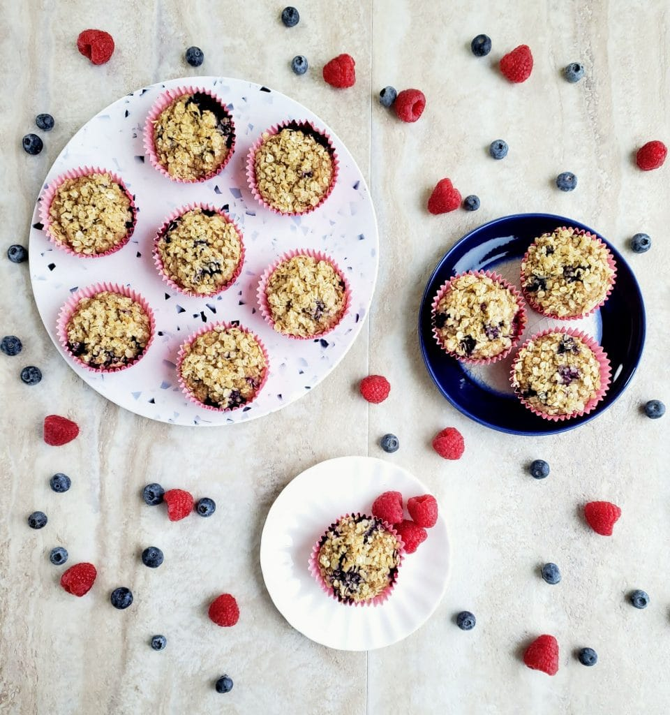Plates of blueberry oatmeal muffins surrounded by raspberries and blueberries