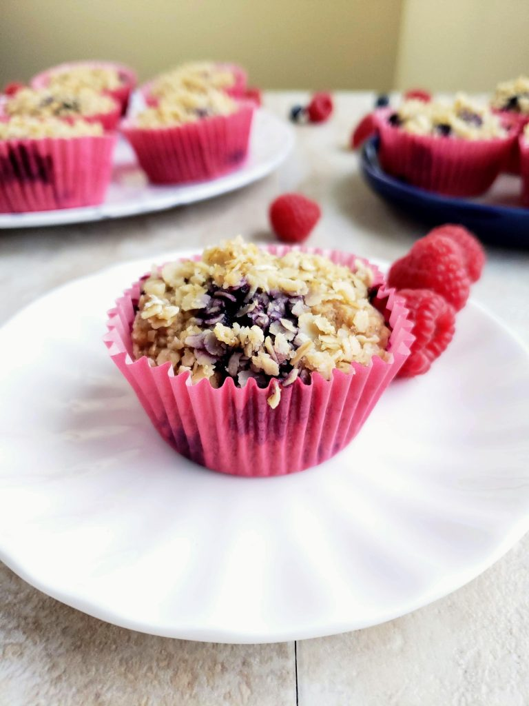 Blueberry oatmeal muffin on a white plate with other muffins behind it