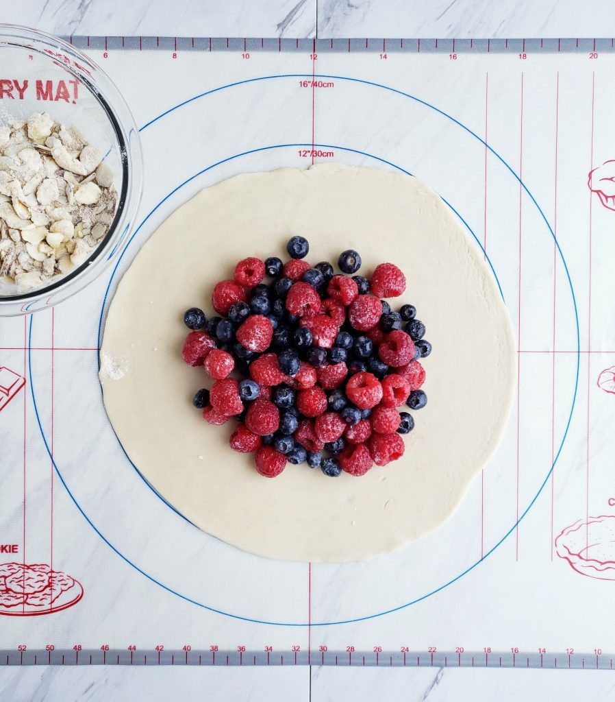 pie crust filled with blueberries and raspberries next to a bowl of almond crumble