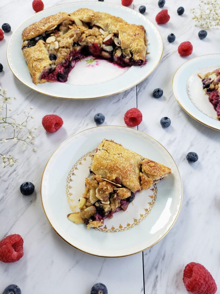 slices of blueberry galette on two plates surrounded by raspberries and blueberries