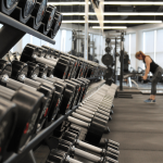 row of dumbbells with a woman working out in the background