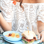 Woman holding a fork full of watermelon. With a smoothie, bowl of fruit and sandwich in front of her