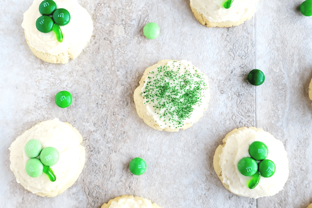 Shamrock cream cheese cookies on a tan background surrounded by green M&M's