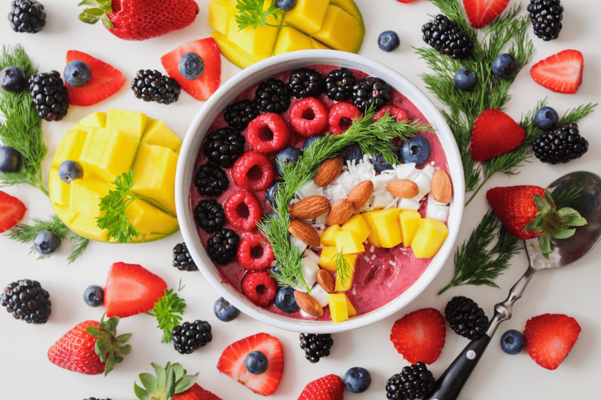 large smoothie bowl surrounded by fresh fruit
