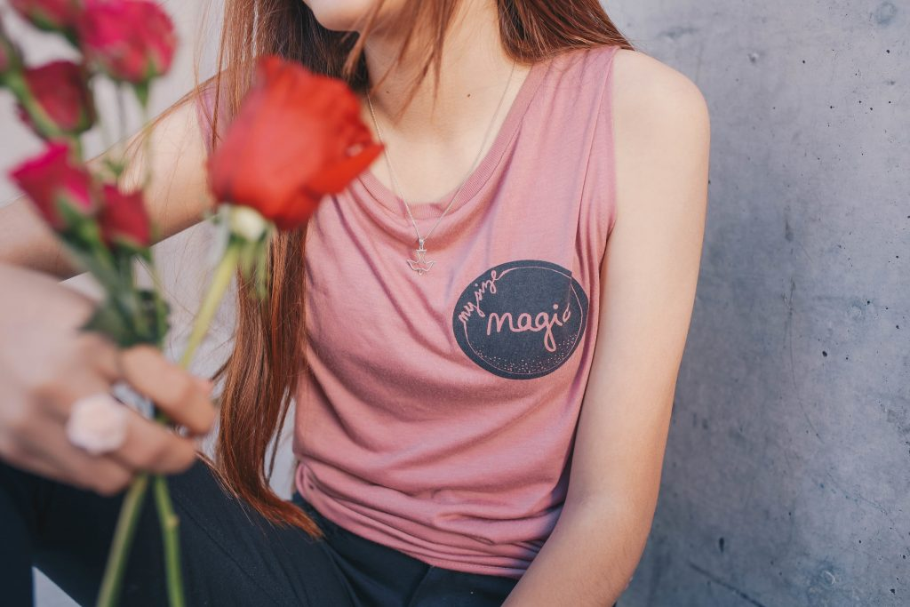 "woman in a ""magic"" pink tank top holding a few roses"
