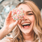 woman holding a donut up to her eye