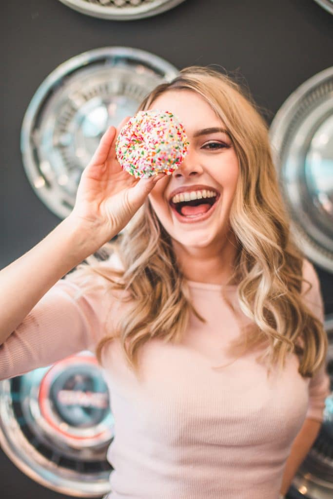 blonde haired girl holding up a donut to her eye