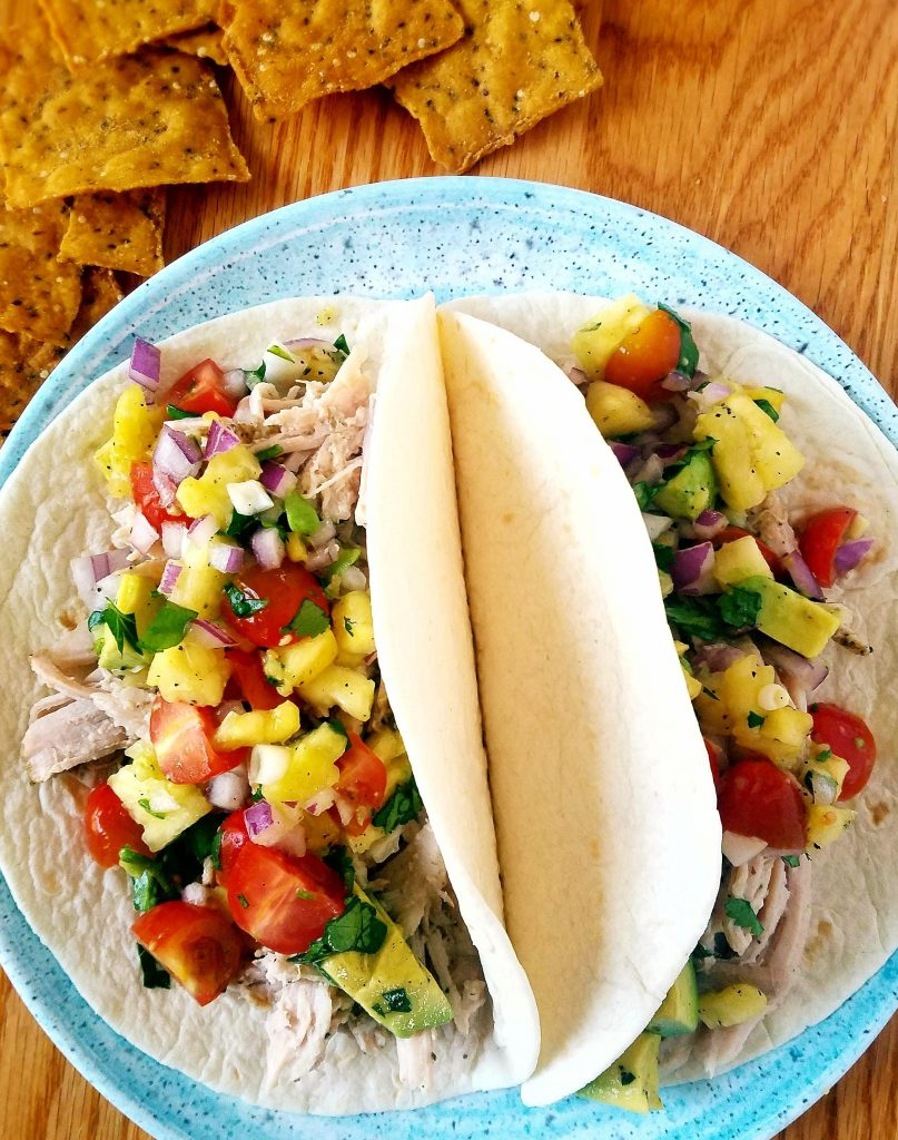 two pork tacos topped with pineapple salsa