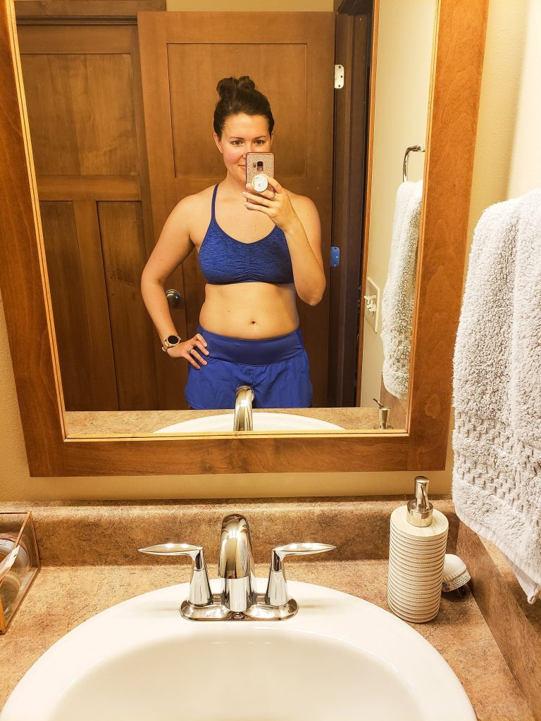 woman standing in a mirror with shorts and a sports bra on
