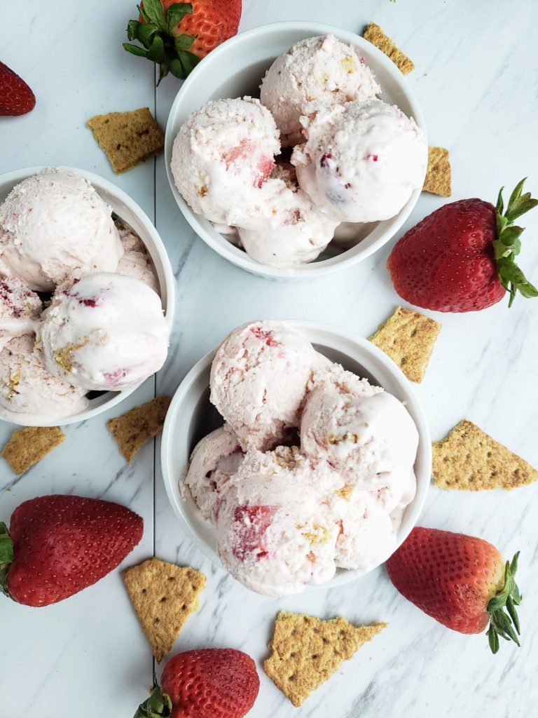 three white ramekins of homemade strawberry cheesecake ice cream