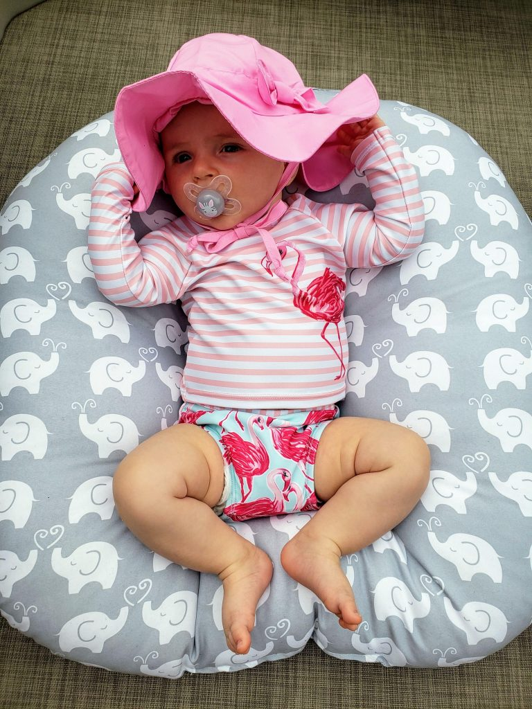 baby in a pink flamingo swim suit with a pink hat, laying in a boppy