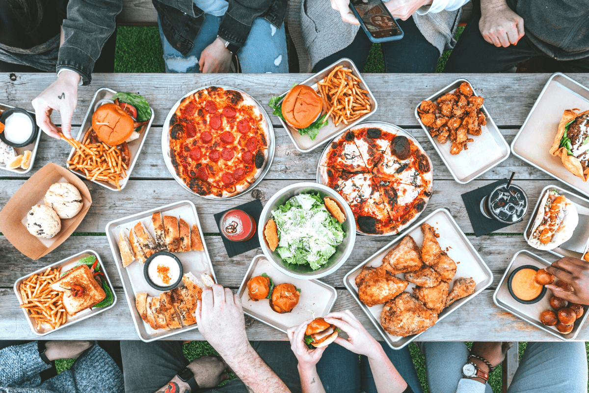 a group of people surrounding a table full of pizza, nachos, fries and more
