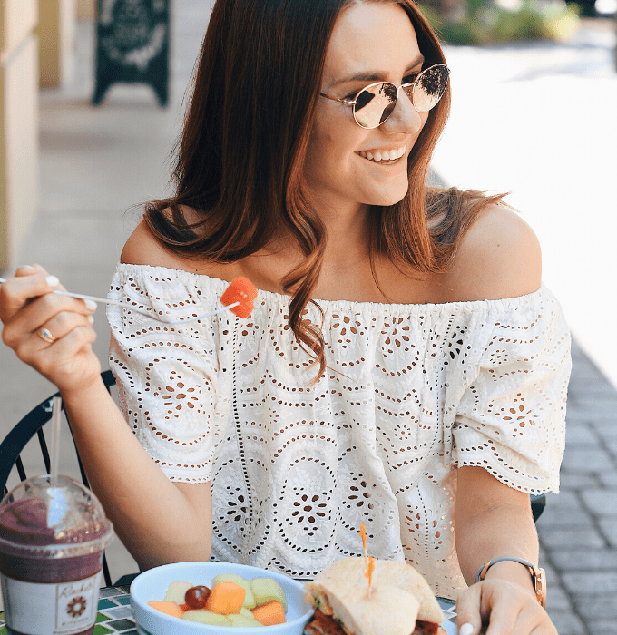 woman in a white top eating a sandwich