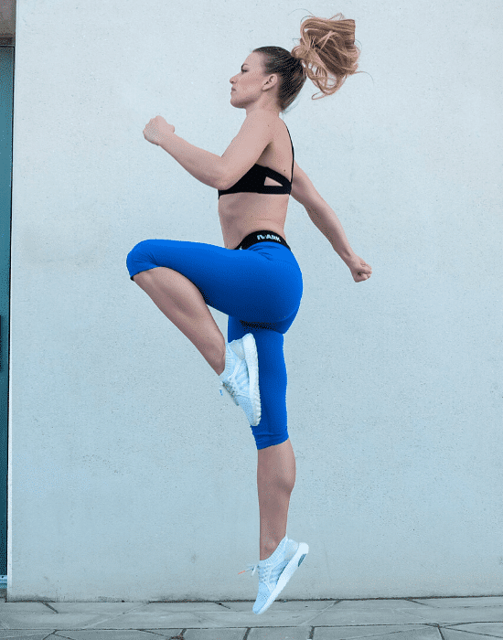 woman in fitness gear jumping in the air