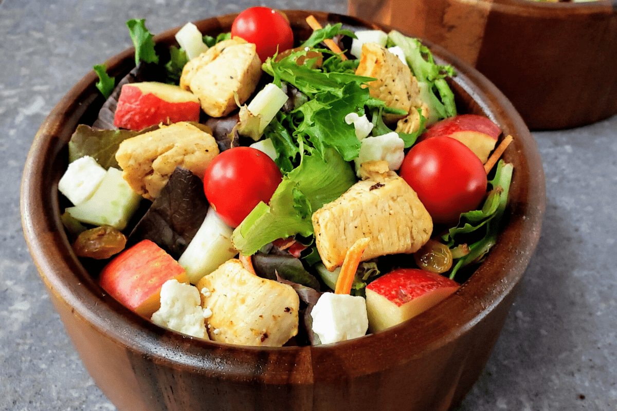 brown bowl filled with salad, chicken and apples