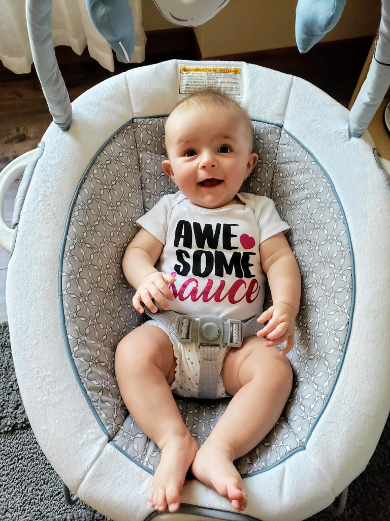 smiling baby sitting in a chair