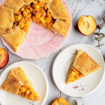 slices of peach cheesecake galette on two plates with the whole pie on a pink plate, surrounded by fresh peaches