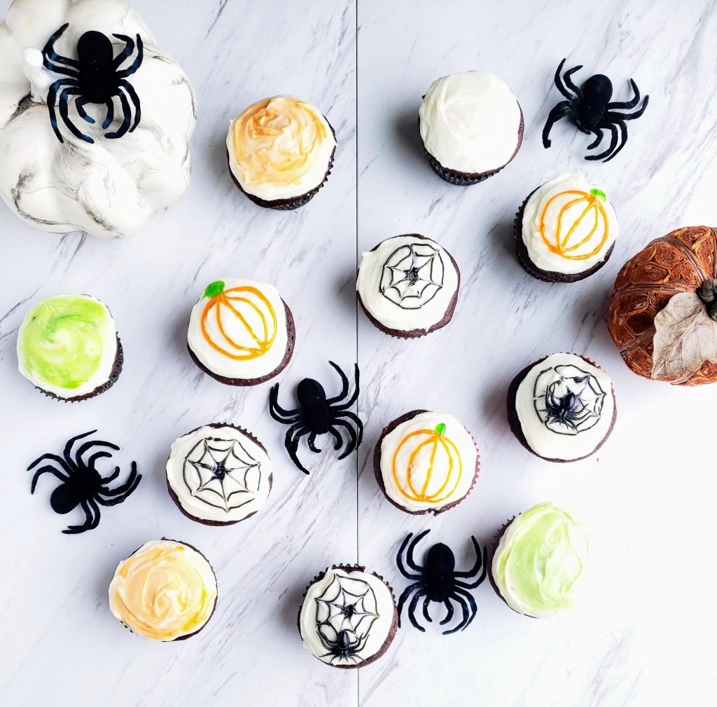 halloween chocolate cupcakes with spiders and pumpkins surrounding them