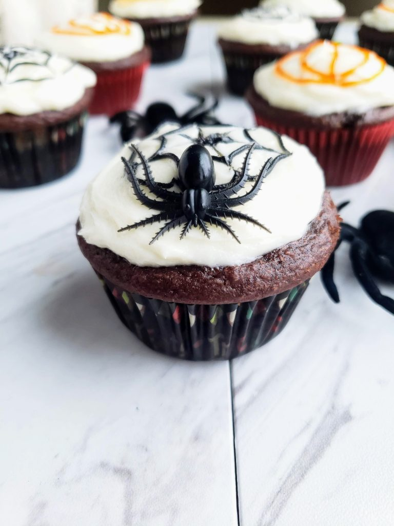 small spider sitting on top of a spider web cupcake