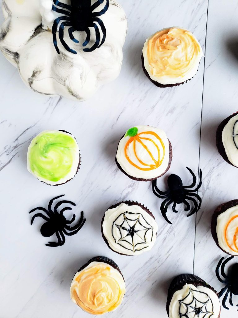 spiders surrounding chocolate cupcakes covered with spider webs, and orange frosting