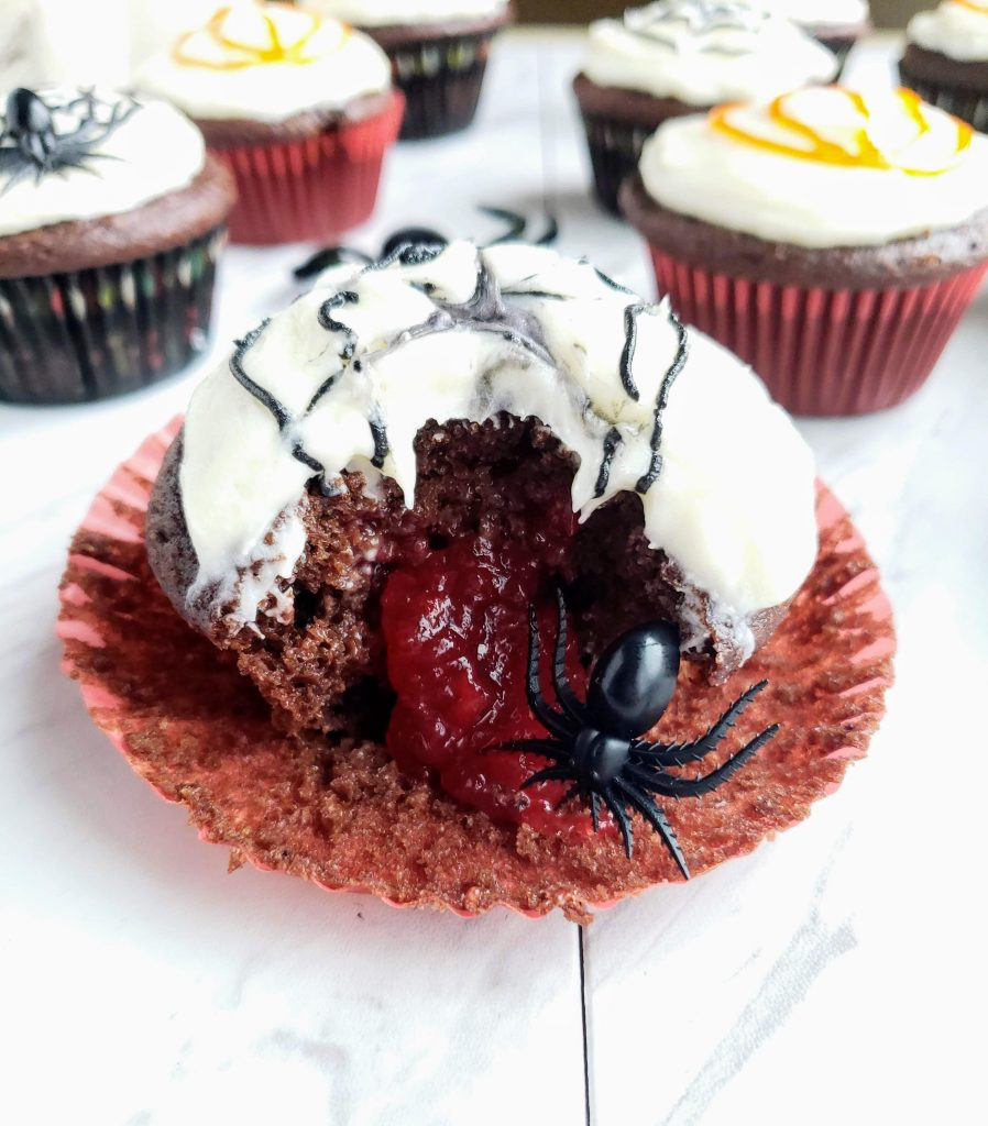 bite taken out of spider web cupcakes with jam coming out the center and a small spider poking out of the jam