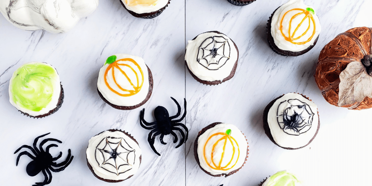 Halloween decorated chocolate cupcakes surrounded by spiders