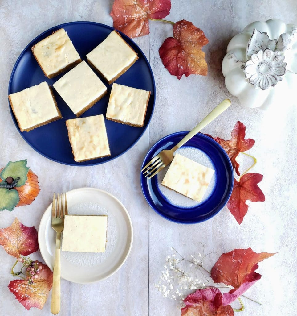 three plates with healthy pumpkin cheesecake bars surrounded by leaves and pumpkins