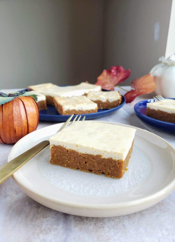 slice of healthy pumpkin cheesecake bar with additional bars on a blue plate behind it
